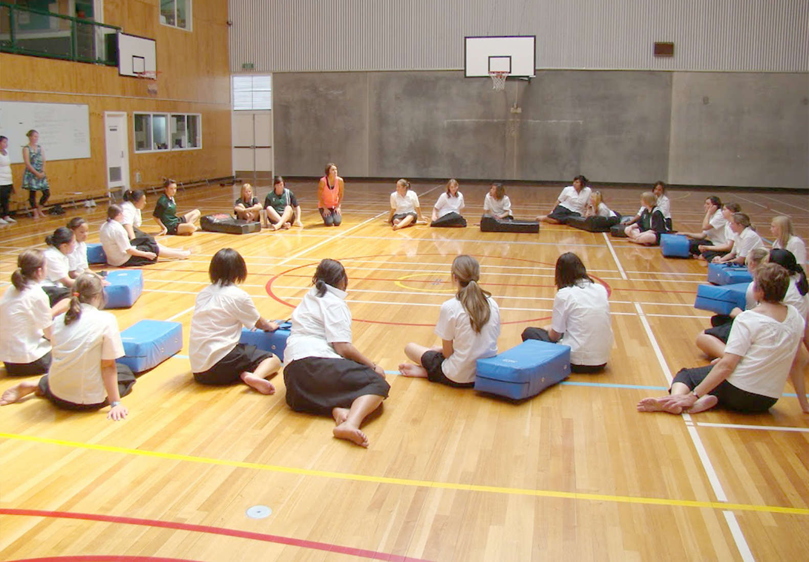 A class of girls sitting and reflecting after some Rock and Water exercises